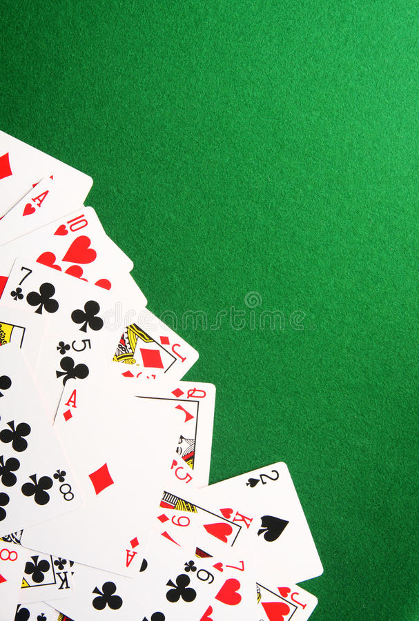 Playing cards on green casino background stock photos