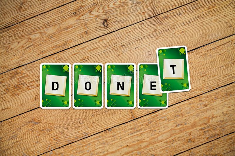 Playing cards with text `Don`t-Done` on a wooden floor royalty free stock image