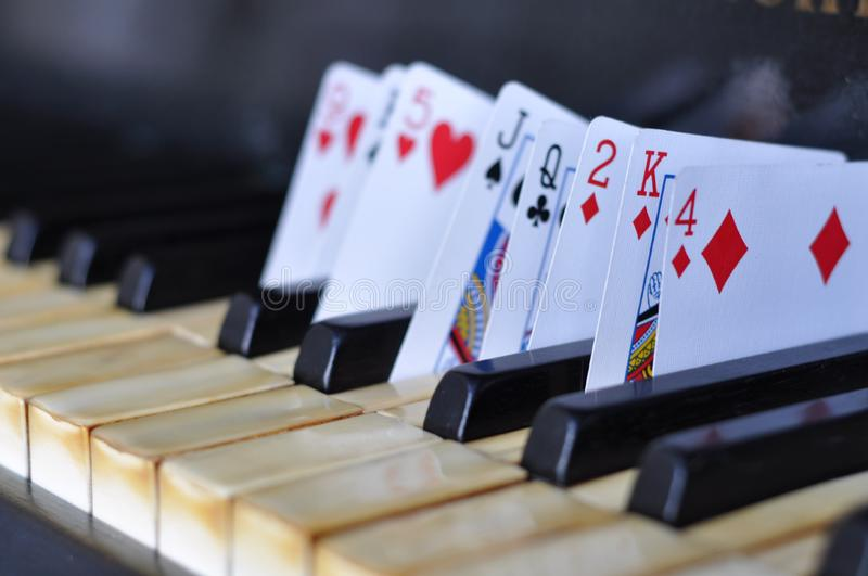 Playing Cards In Between Piano Keys royalty free stock image