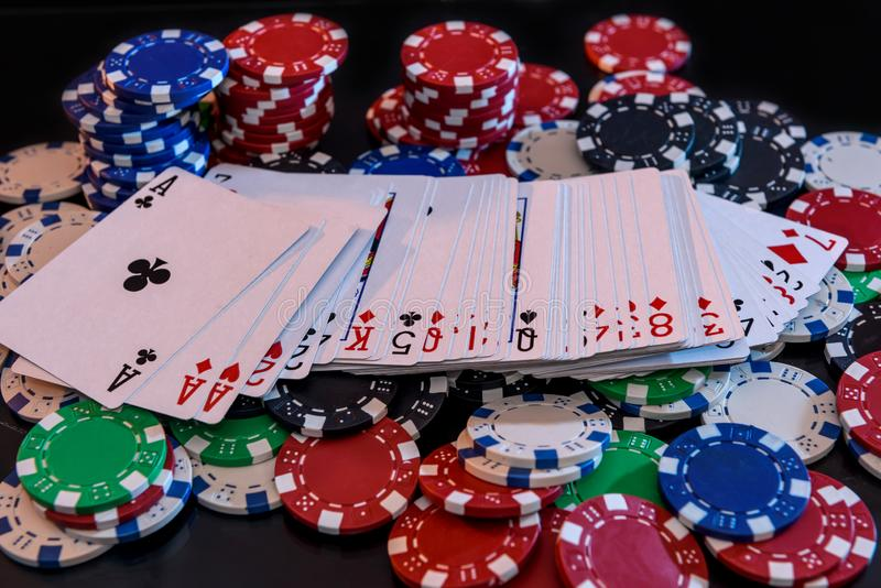 Playing cards with poker chips at black background royalty free stock photography