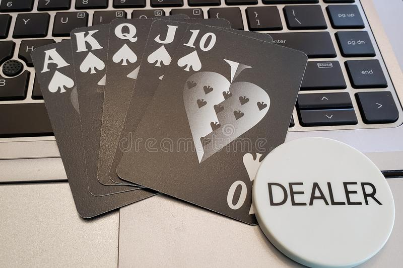 A straight flush poker hand with dealer button. Playing cards showing a straight flush with a dealer button on a laptop computer keyboard. Online gambling and stock photo