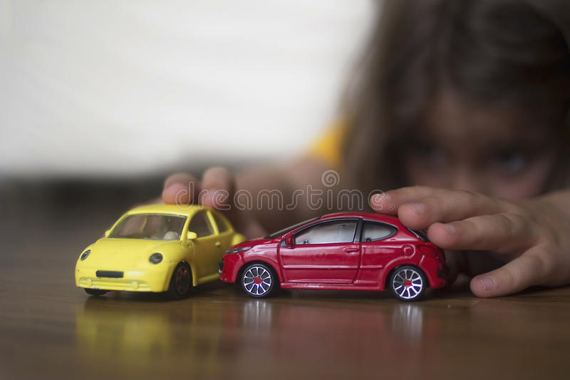 Playing with cars. Young caucasian girl playing with model cars stock photos
