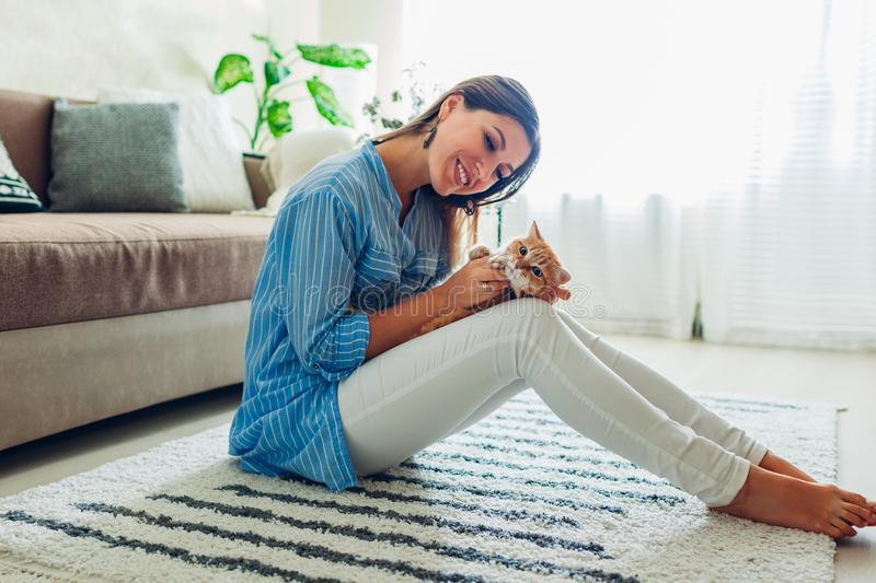 Playing with cat at home. Young woman sitting on carpet and hugging pet stock photos