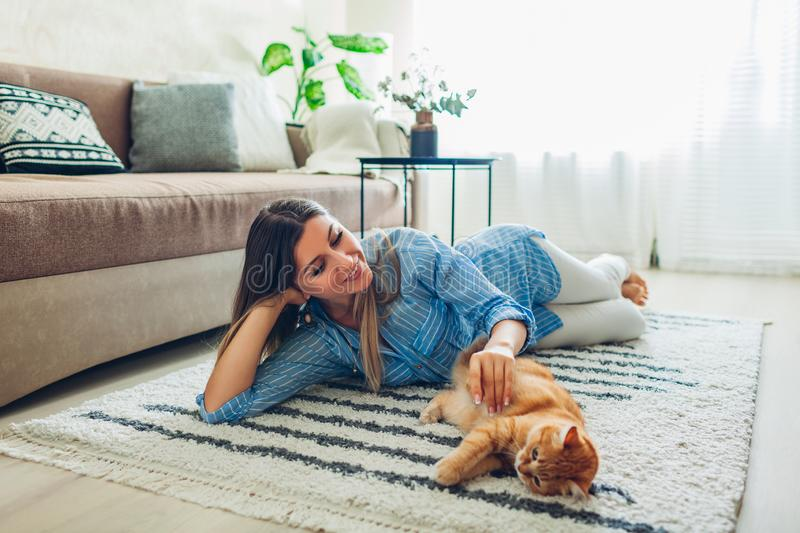 Playing with cat at home. Young woman lying on carpet and teasing pet stock photos