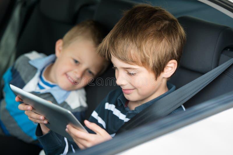 Playing children. Children playing through ipad touchscreen inside the car