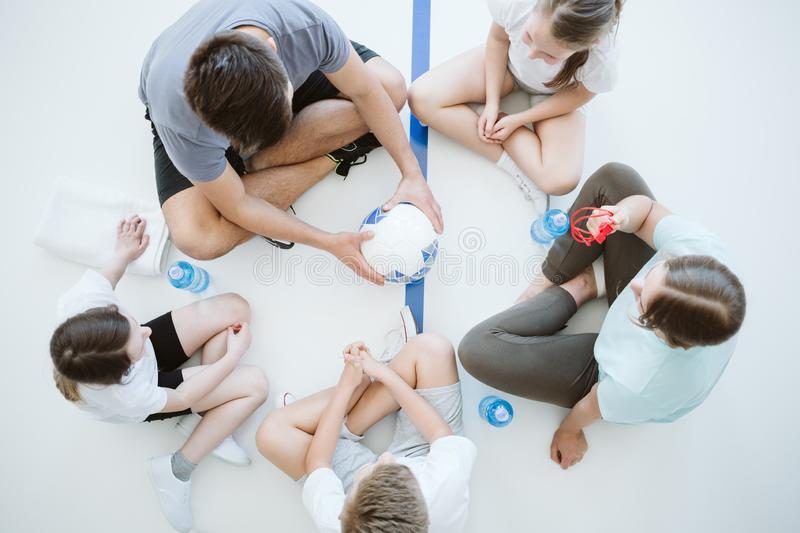 Playing in the circle. Group of kids and a coach playing in the circle with the ball royalty free stock images