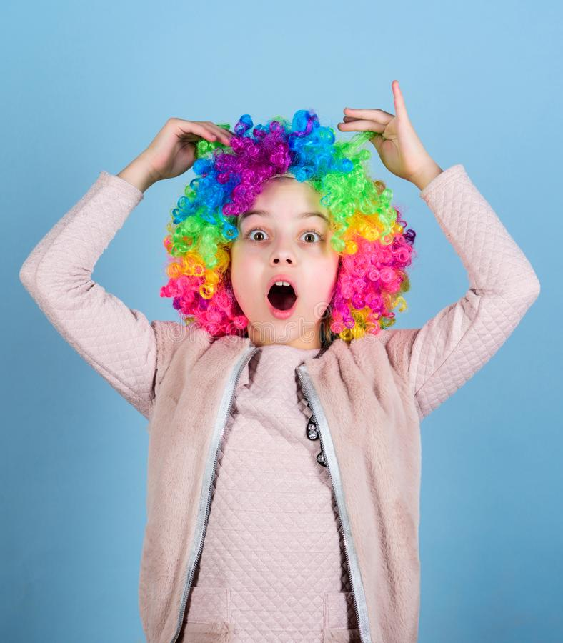Playing the clown. Adorable small clown with opened mouth. Cute little girl wearing colorful clown wig hair. She is a royalty free stock photography