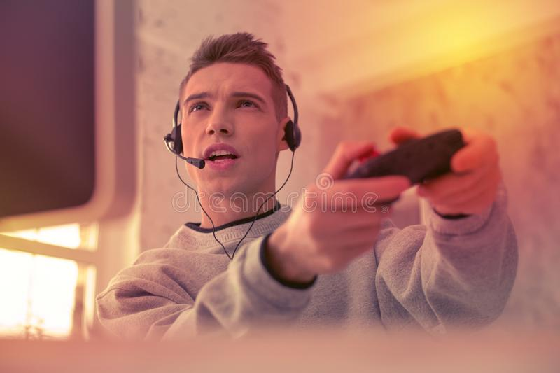 Young concentrated man enthusiastically playing with computer royalty free stock photography
