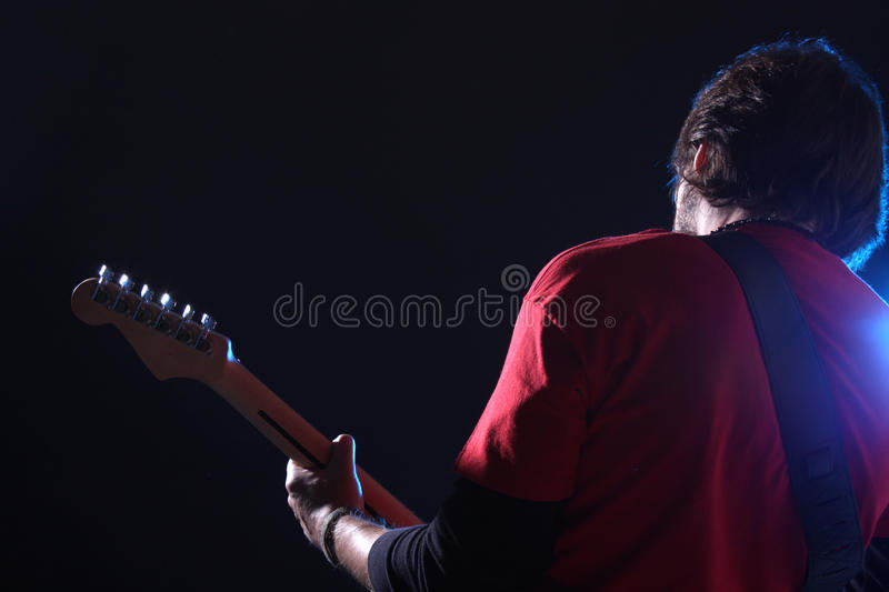 Playing electric guitar. Musician playing electric guitar on stage royalty free stock photo