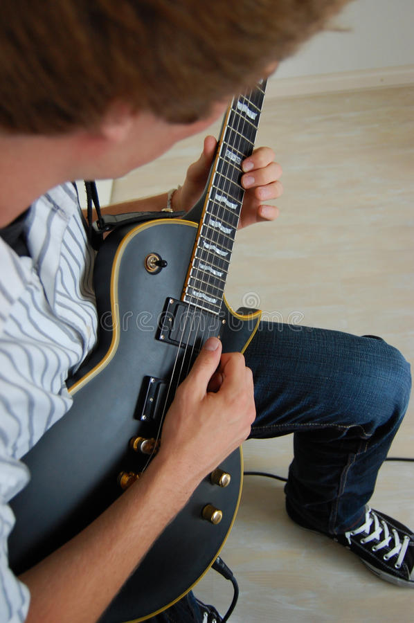 Playing Electric Guitar. A young man playing a black electric guitar royalty free stock photography