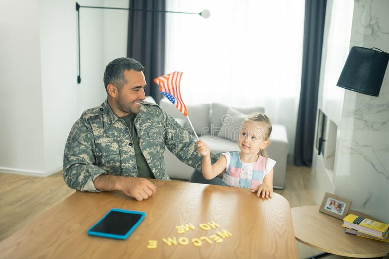 Girl playing with American flag while meeting daddy at home royalty free stock photos