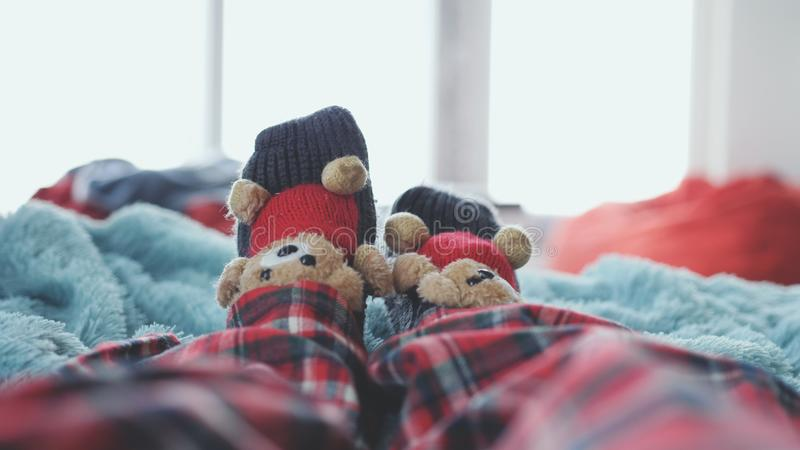 Playing foot at home in bed dressed socks with cute teddy bears and in pajamas against the background of a blurred. Playing foot at home in bed dressed socks royalty free stock photo