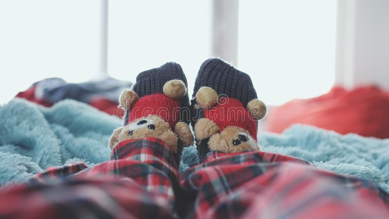 Playing foot at home in bed dressed socks with cute teddy bears and in pajamas against the background of a blurred. Playing foot at home in bed dressed socks royalty free stock images