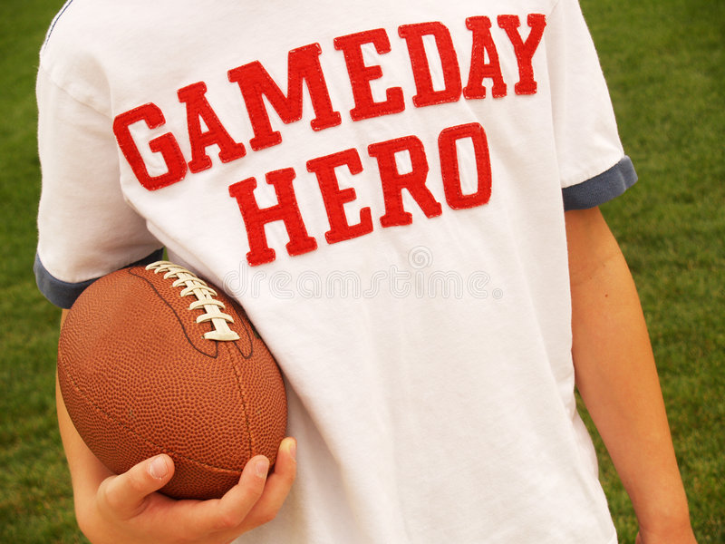 Playing football. Male holding an American football and wearing a Gameday Hero shirt stock photography