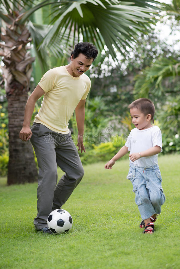 Playing football. Vertical image of a father playing football with his little son on the backyard royalty free stock photography