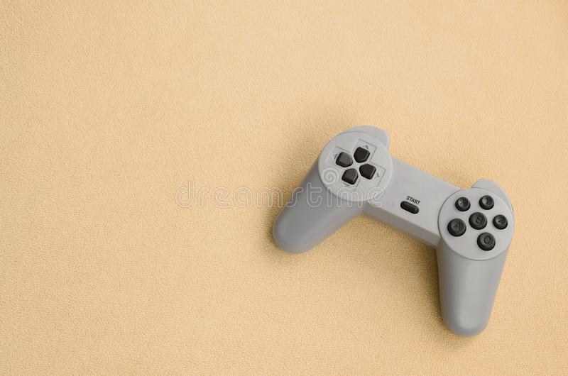 Playing games concept. Single pad joystick lies on the blanket of furry orange fleece fabric. Controller for video games on a. Background texture of light royalty free stock photos