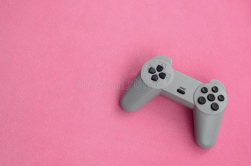 Playing games concept. Single pad joystick lies on the blanket of furry pink fleece fabric. Controller for video games on a backgr. Ound texture of light pink stock photography