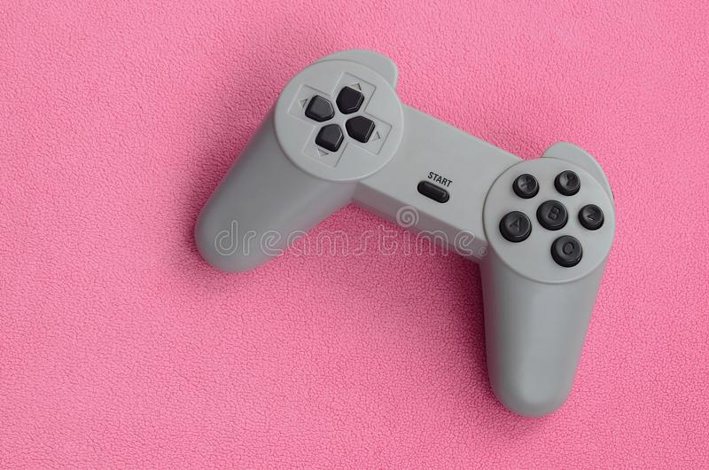 Playing games concept. Single pad joystick lies on the blanket of furry pink fleece fabric. Controller for video games on a backgr. Ound texture of light pink stock images
