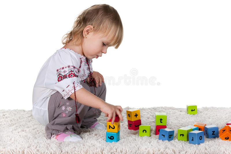 Playing girl in the embroidered blouse. A cheerful little girl in the embroidered traditional ukrainian blouse is playing colorful blocks on the white carpet stock photos