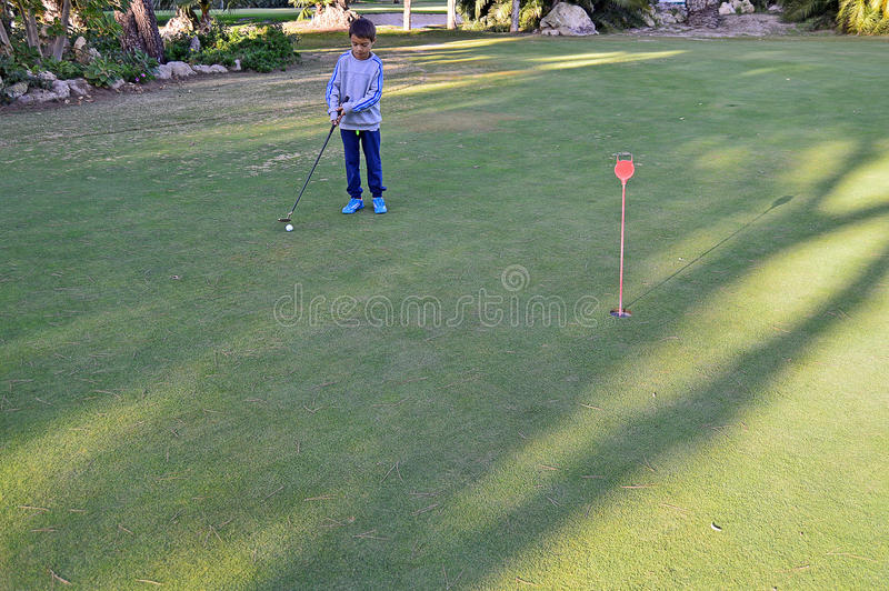 Playing Golf - A Boy Putting With Oversize Putter. stock photos
