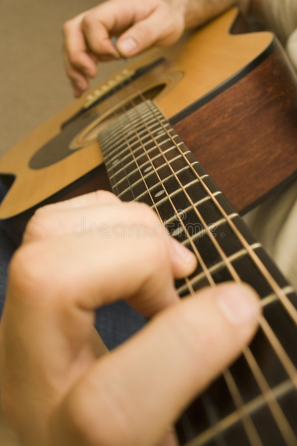 Playing Guitar. Shot of hands playing an accoustic guitar with a plectrum stock images