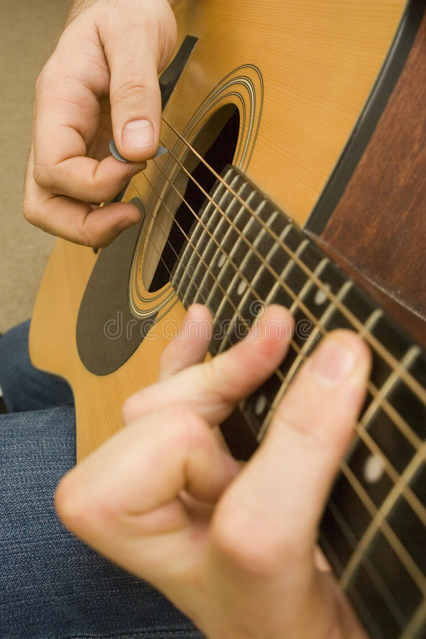 Playing Guitar. Shot of hands playing an accoustic guitar with a plectrum stock image
