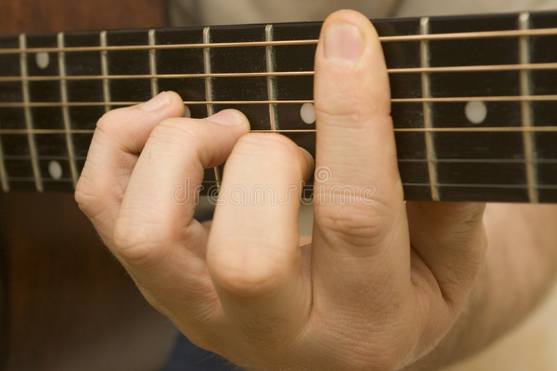 Playing Guitar. Close up shot of a chord on the fret board of an accoustic guitar stock photo