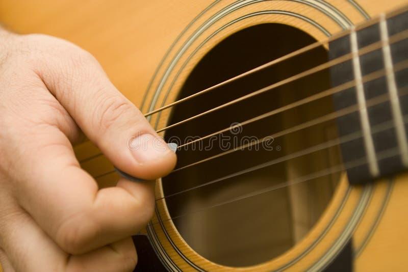 Playing Guitar. Close up of hands playing an accoustic guitar stock photos