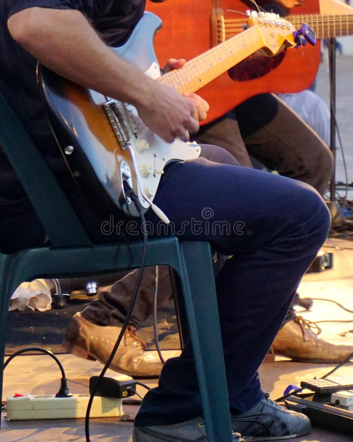 Playing guitar. Band playing guitar during concert stock photo