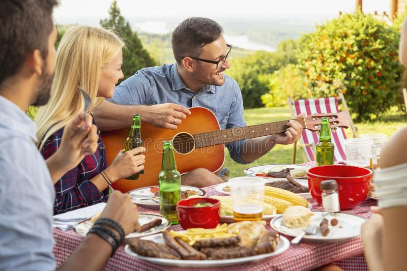 Playing the guitar at barbecue party royalty free stock photos
