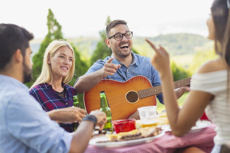 Playing the guitar at a barbecue party royalty free stock photo