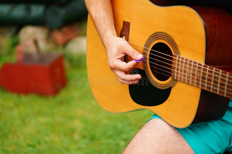 Playing the guitar. Close-up of a person playing accoustic guitar stock images