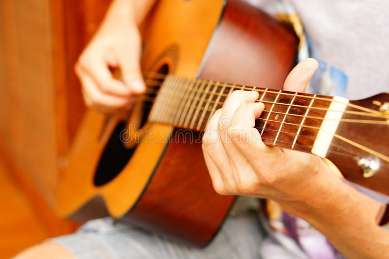 Playing the guitar. Close-up of a person playing accoustic guitar royalty free stock photography