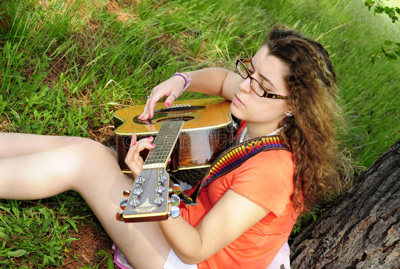 Teenage Girl Playing Guitar In Woods royalty free stock photos