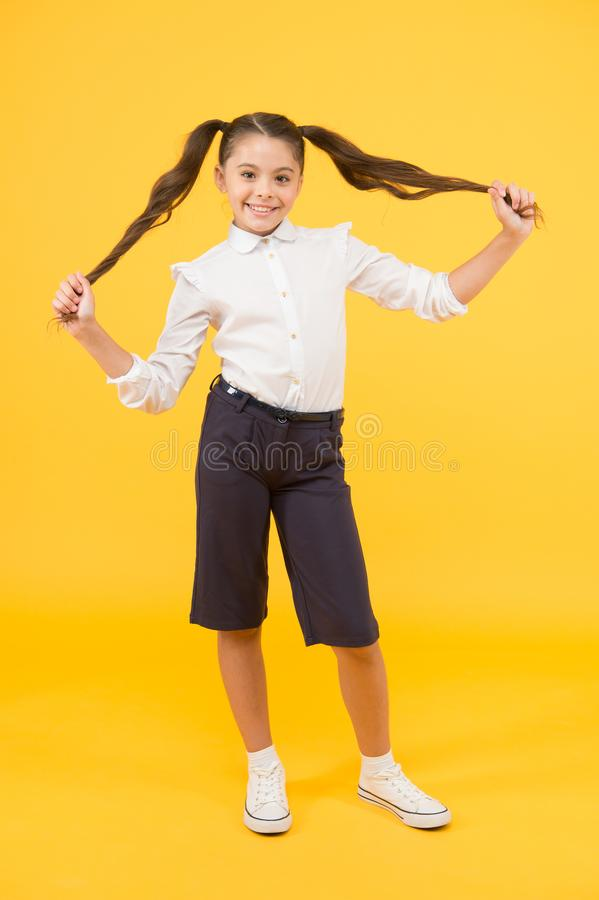 Playing with hair. Schoolgirl happy smiling pupil long hair. Beginning of academic year. Adorable schoolgirl. Time to. Study. Ready for lesson. School fashion stock photo