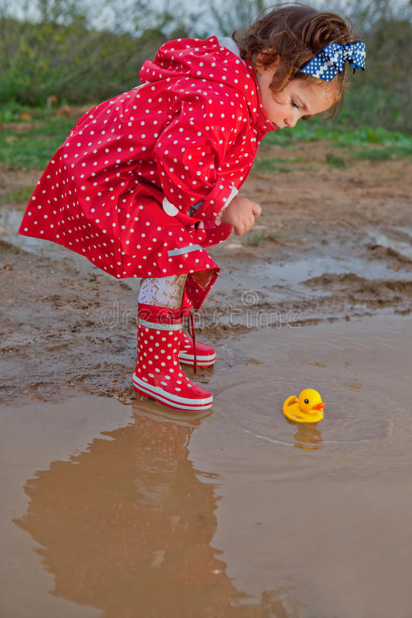 Playing with her water toys on muddly puddles. Baby girl dressed with dotted raincoat and rainboots playing with her water toys on muddly puddles stock photography