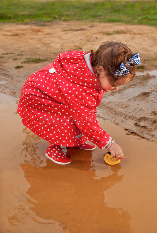Playing with her water toys on muddly puddles. Baby girl dressed with dotted raincoat and rainboots playing with her water toys on muddly puddles royalty free stock photo
