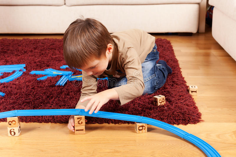 Playing at home. Little boy is building toy railroad using bricks stock photos