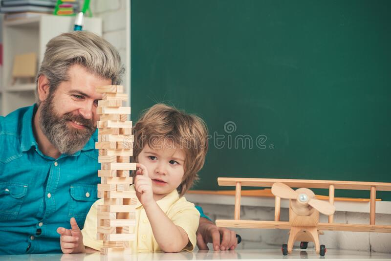 Playing Jenga. Cute little preschool kid boy with teacher playing in a classroom. Learning and education concept. Father. Looking at son playing jenga game royalty free stock photos