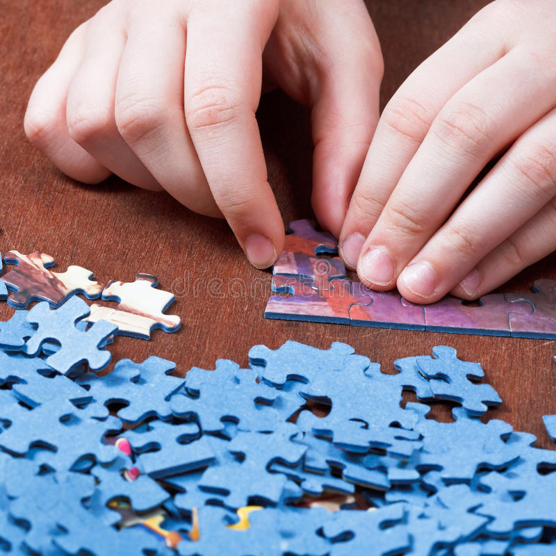 Playing with jigsaw puzzles. On wooden table stock photos