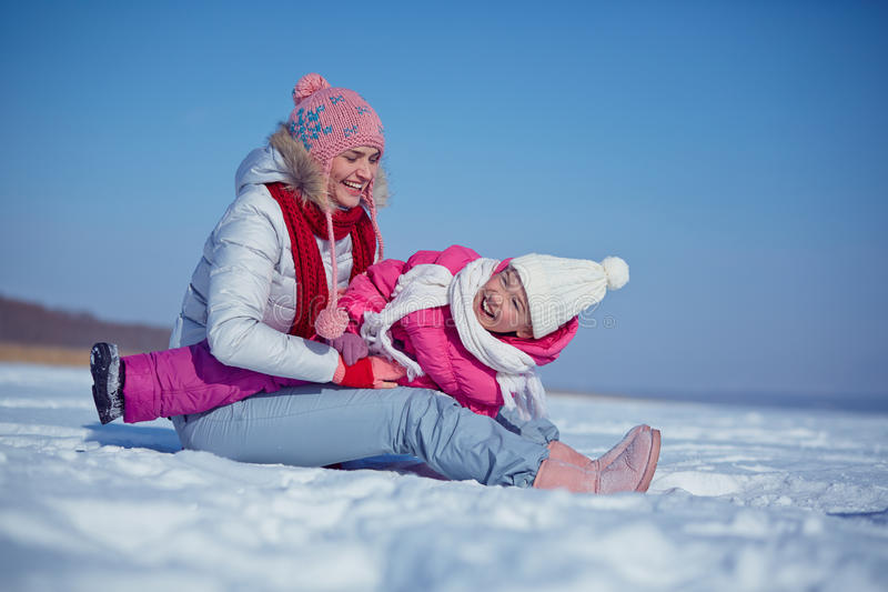 Playing with kid. Happy female in winterwear playing with her daughter in snowdrift stock images