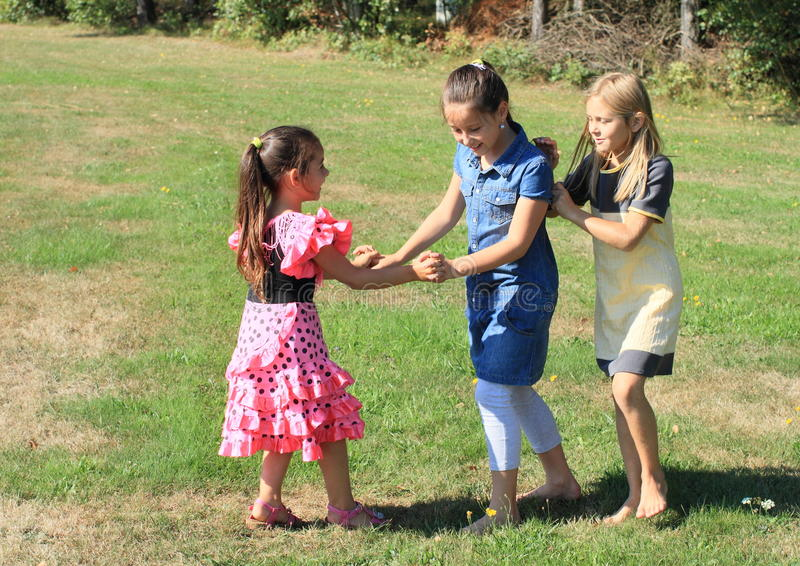Playing kids. Three happy little girls in dresses playing on green meadow stock photography