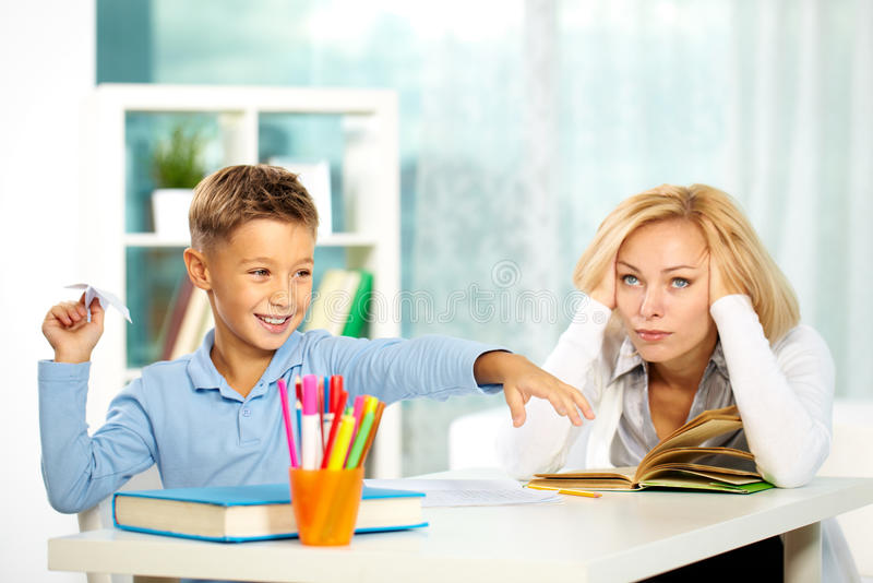 Playing during lesson. Portrait of naughty boy playing with paper plane during lesson and annoyed tutor touching her head royalty free stock images