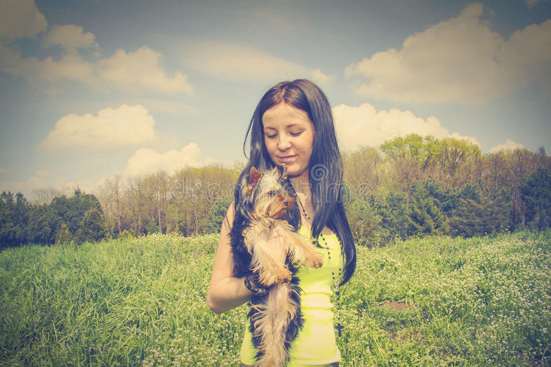 Playing with little Yorkshire Terrier. Sweet girl Playing with little Yorkshire Terrier stock photo