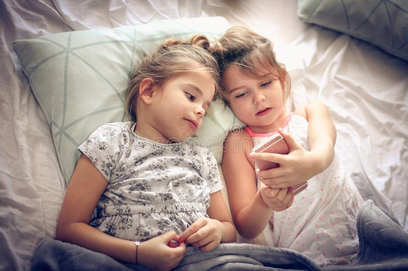 Playing with mobile phone. Two little girl using smart phone together royalty free stock photography