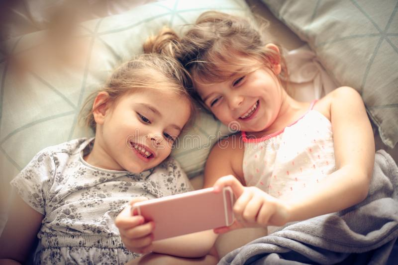 Playing with mobile phone. Two little girl using smart phone together stock image
