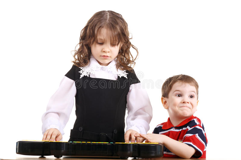 Playing the music. Little children playing with the toy composer royalty free stock photos
