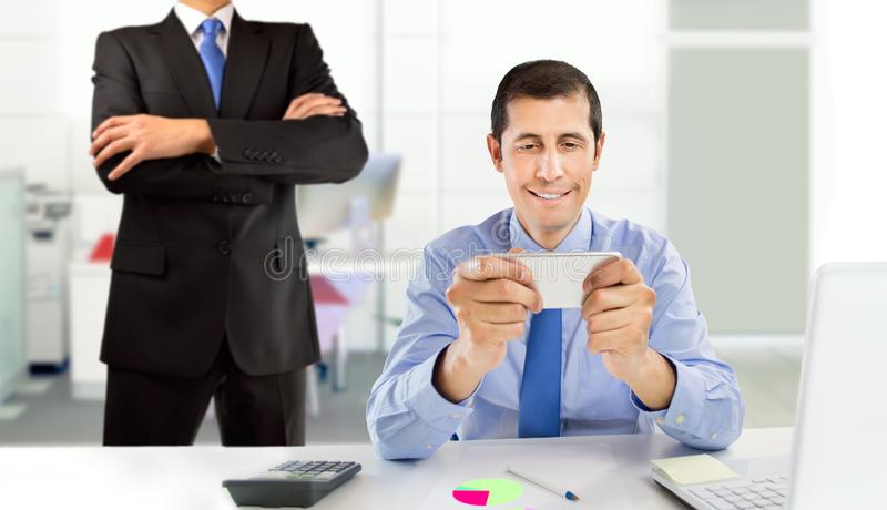 Playing at the office. Lazy employee playing games with his smartphone sitting in a desktop while his angry boss is watching at the office royalty free stock photography