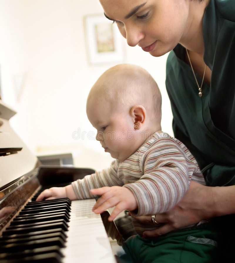Playing the piano 2. It is a very intimate moment. A baby is enjoying the piano while his mother is seeing after him