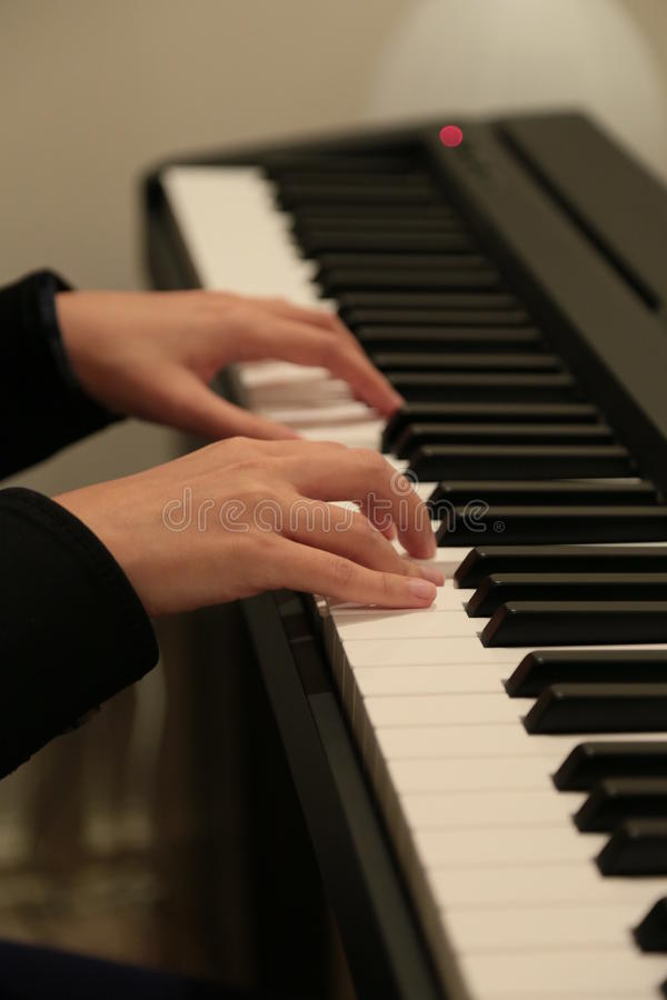 Playing The Piano. A girl playing electronic piano stock image
